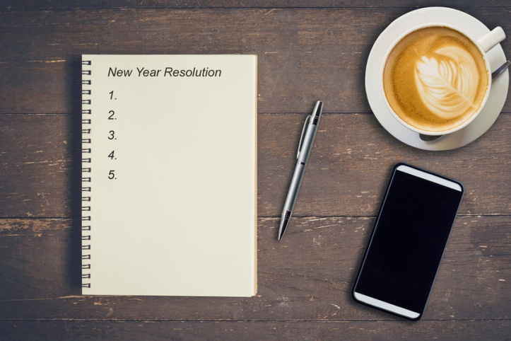 Business concept - Top view notebook writing New Year Resolution, pen, coffee cup, and phone on wood table.